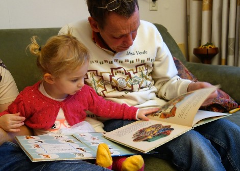 A dad and his daughter read together in a lounge room