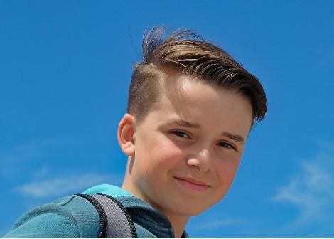 A boy wearing a schoolbag spends time outside