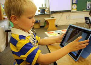 A boy uses an ipad in the classroom